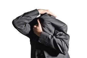男性が顔をジャケットで覆っている画像