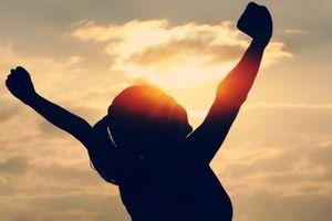 女性が空に向けてガッツポーズ画像